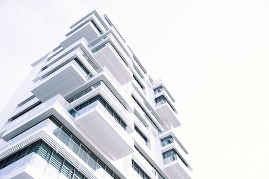 Weißes Bürogebäude von unten fotografiert