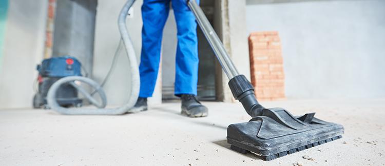 Mitarbeiter reinigt die Baustelle mit einem Sauger