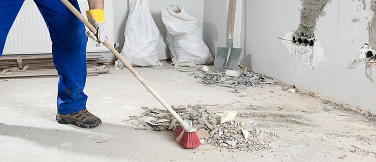 Mitarbeiter führt eine Baureinigung in Berlin durch indem er den Boden fegt