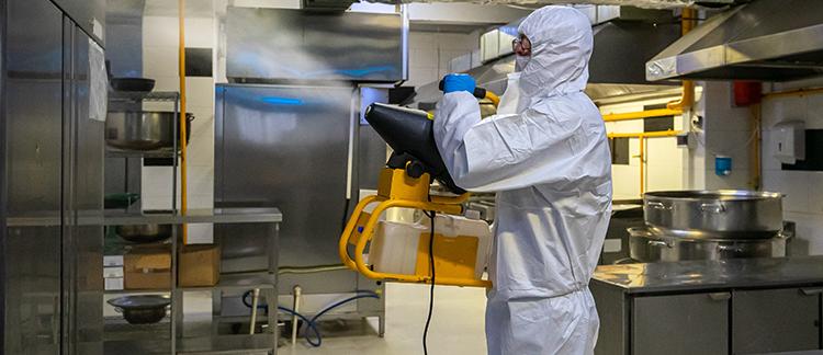 Mitarbeiter führt eine Desinfektion in einer Restauratküche durch
