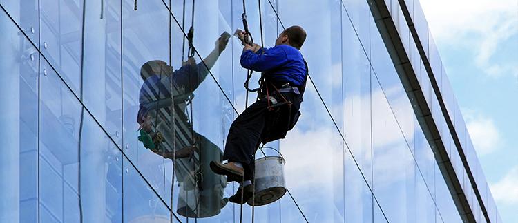 Mitarbeiter führt eine Glasreinigung von außen eines Gebäudes durch
