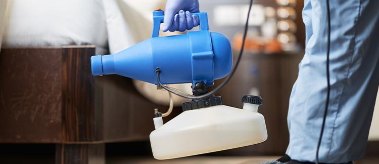 Mitarbeiter hält einen Vernebler für die Raumdesinfektion in der Hand