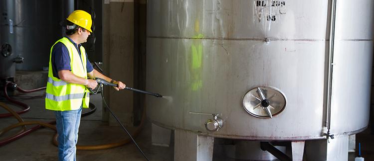 Mitarbeiter reinigt Industrielle Maschinen